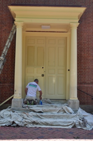 A man painting the meeting house's door