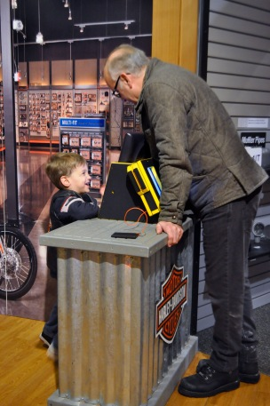 Sebastian and Pop Pop purchasing parts from the mock Harley store.